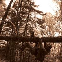 man swinging across log bridge