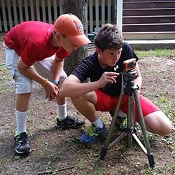 two boys set up a camera on a tripod