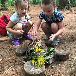 two girls build a fairy house