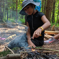 girl builds a fire in the woods