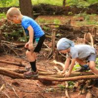 young children balance crossing log