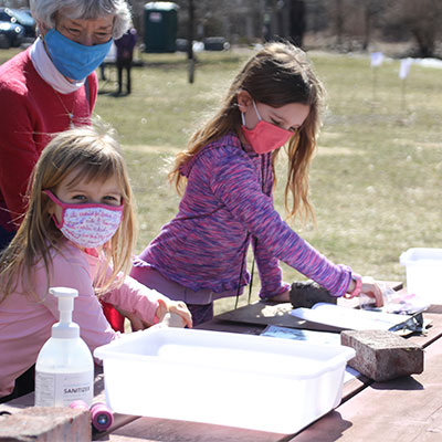 two girls make a craft at picninc table outside on earth day