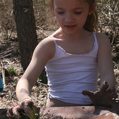 child making sculpture from mud
