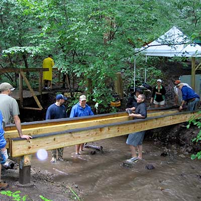 team of volunteers installs new bridge over the stream along the trail at Baltimore Woods