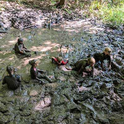 camp group in swamp at baltimore woods covered in mud