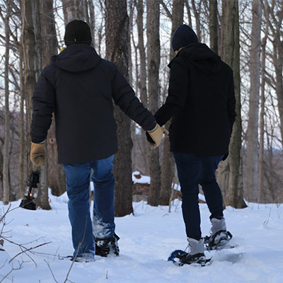 two-snowshoers at Baltimore Woods on a trail carrying an old fashioned kerosene lantern