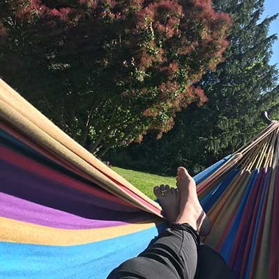 feet stretched out in a colorful hammock
