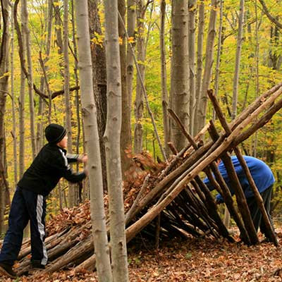 two boys build a fort in the forest in fall