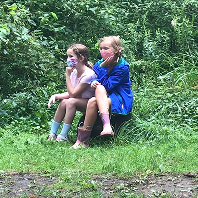 two grsl sittng on a log in a field watching the world go by