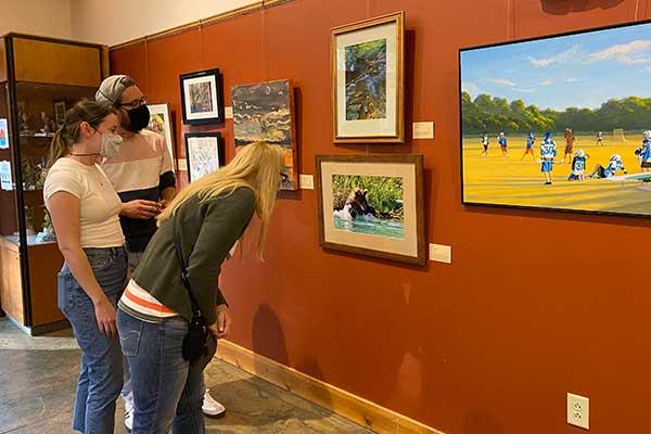 members-show-visitors-looking at art