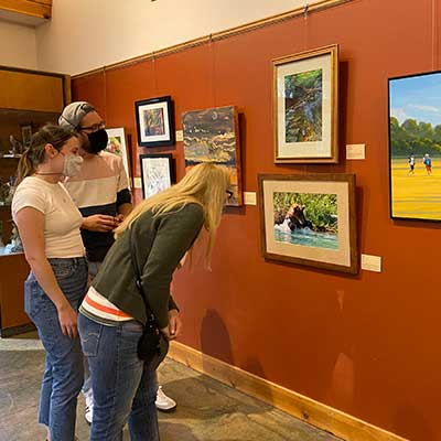 visitors looking at art on gallery wall